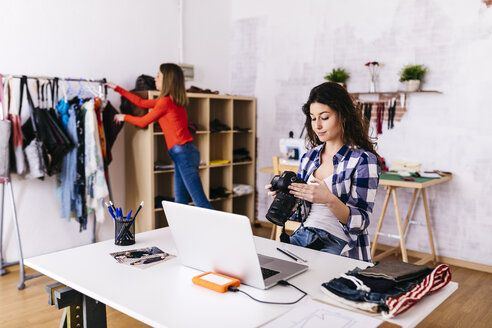 Fashion designer with camera and laptop in studio - JRFF01579