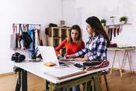 Two fashion designers with laptop in studio taking notes - JRFF01582
