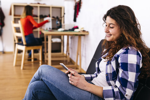 Smiling young woman in fashion studio using cell phone with woman in background on sewing machine - JRFF01594