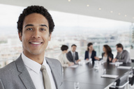 Portrait of smiling businessman in conference room - CAIF00010