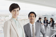Portrait of smiling businessman and businesswoman in conference room - CAIF00025