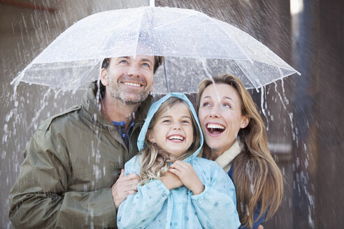 Enthusiastic family under umbrella in downpour - CAIF00046