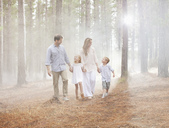 Happy family walking in sunny woods - CAIF00061