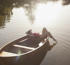Serene woman sunbathing in boat on lake - CAIF00082