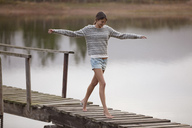 Woman walking on dock over lake with arms outstretched - CAIF00088