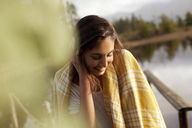 Smiling woman wrapped in blanket at lakeside - CAIF00094