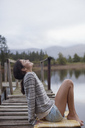 Smiling woman sitting on dock at lakeside with head back - CAIF00097