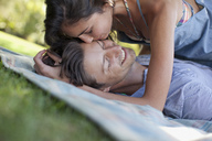 Affectionate couple laying on blanket in grass - CAIF00103