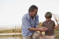 Smiling grandfather and grandson fishing at lakeside - CAIF00115