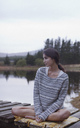 Pensive woman sitting on dock at lake - CAIF00118