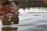 Smiling couple swimming in lake - CAIF00136