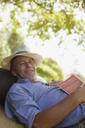 Portrait of smiling man laying in grass with book - CAIF00139