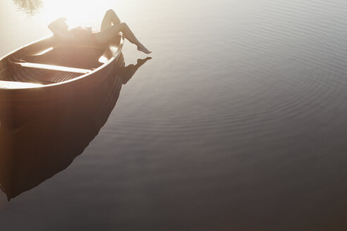 Woman laying in boat on sunny lake - CAIF00166