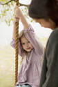 Portrait of girl on swing with mother - CAIF00172