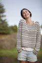 Portrait of smiling woman with hands in short pockets - CAIF00181