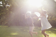 Boy and girl holding hands and running with butterfly nets in grass - CAIF00193