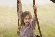 Portrait of smiling girl on swing - CAIF00199