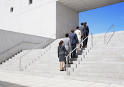 Business people standing in a row on urban stairs - CAIF00217