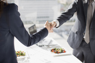 Businessman and businesswoman shaking hands at table with lunch - CAIF00220