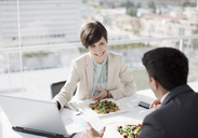 Businessman and businesswoman with laptop meeting over lunch - CAIF00223