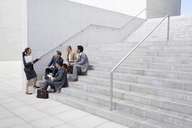 Business people meeting on urban stairs - CAIF00256