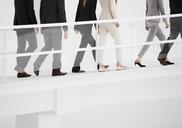 Business people ascending elevated walkway - CAIF00271