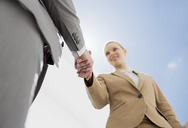 Smiling businesswoman shaking businessman's hand - CAIF00274