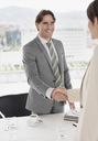 Businessman and businesswoman shaking hands at restaurant table - CAIF00283