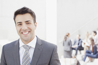 Portrait of smiling man with co-workers in background - CAIF00286