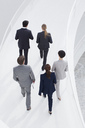 Business people ascending elevated walkway - CAIF00298