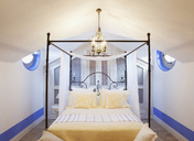Chandelier over four poster bed in luxury bedroom - CAIF00364