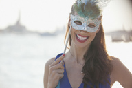 Portrait of smiling woman wearing mask at waterfront in Venice - CAIF00452