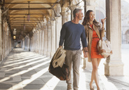 Smiling couple walking along corridor in Venice - CAIF00461
