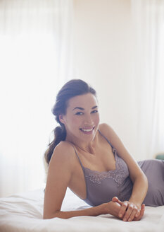 Portrait of smiling woman in nightgown laying on bed - CAIF00467