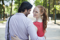 Portrait of smiling woman walking with boyfriend in park - CAIF00479