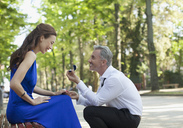 Man with engagement ring proposing to girlfriend in park - CAIF00485