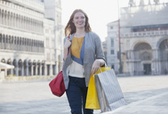 Smiling woman carrying shopping bags through St. Mark's Square in Venice - CAIF00503