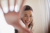 Portrait of smiling woman with hand outstretched - CAIF00509