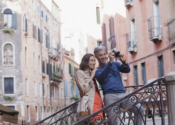 Smiling couple taking photograph in Venice - CAIF00545