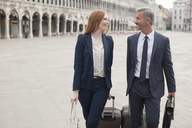 Smiling businessman and businesswoman pulling suitcases through St. Mark's Square in Venice - CAIF00566