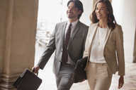 Smiling businessman and businesswoman walking - CAIF00581