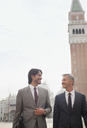 Smiling businessmen walking in St. Mark's Square in Venice - CAIF00596