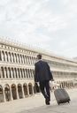 Businessman pulling suitcase through St. Mark's Square in Venice - CAIF00599