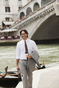 Portrait of smiling businessman with coffee walking along canal in Venice - CAIF00605