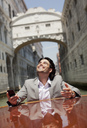 Enthusiastic businessman riding on boat through canal in Venice - CAIF00608