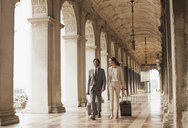 Smiling businessman and businesswoman pulling suitcases along corridor in Venice - CAIF00623