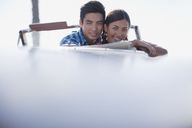 Smiling couple sitting in convertible - CAIF00707