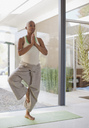 Older woman practicing yoga in home - CAIF00719