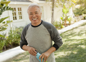 Smiling older man carrying water bottle - CAIF00734