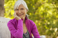 Smiling older woman sitting outdoors - CAIF00737